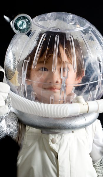 Asian boy in a homemade astronaut suit on a black background.  There is a tube around his helmet.  He is giving a thumbs up with his right hand.